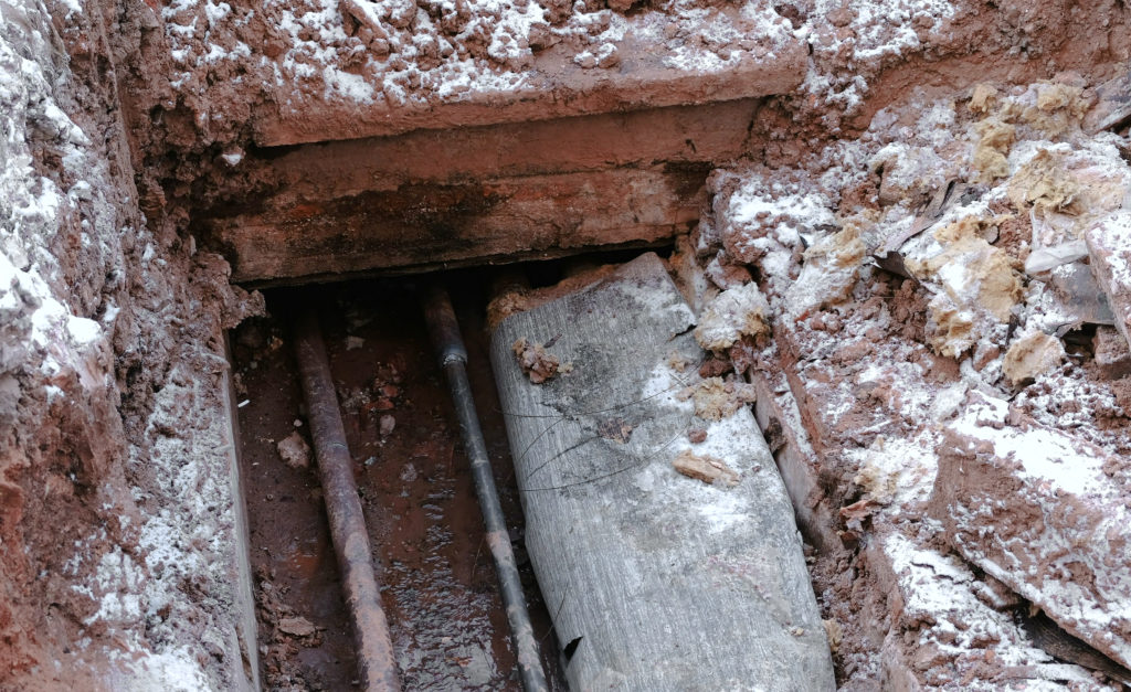 Crash, burst pipes and leaking water under the earth. Excavated pipes in the winter.